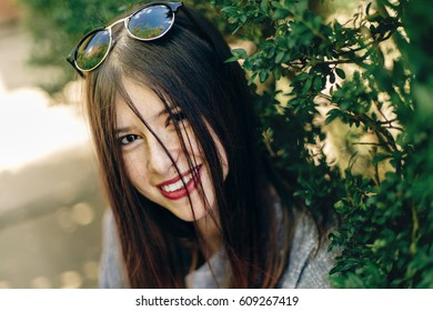 stylish beautiful hipster woman smiling near green leaves in sunny park. young girl with sunglasses with beautiful smile in botanical garden in spring. space for text. joyful moment