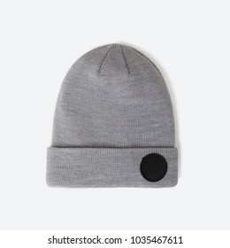 Stylish beautiful knitted wool sports cap with black circle for logo inscription on a gray background, mock up, grey