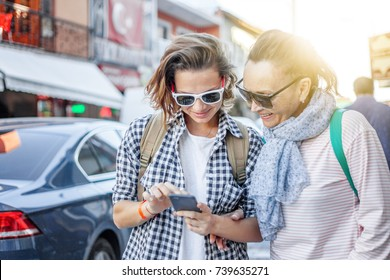 Stylish and beautiful mature mother and adult daughter travel together, walk along the street and use mobile phone navigator . Family, travel, shopping, joy, communication