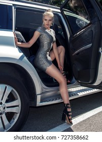 Stylish beautiful sexy blonde woman posing in elegant dress. Fashionable young woman in elegant dress. Rich woman getting out of luxury car. Luxury Lifestyle. Luxury Woman