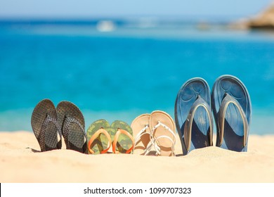 Stylish beautiful slippers in the sand on the sea background