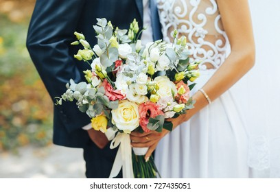 stylish and beautiful wedding bouquet in the hands of the bride and groom