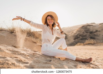 stylish beautiful woman in desert sand in white outfit wearing straw hat on sunset, travel safari on vacation