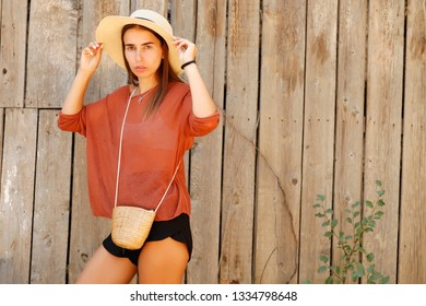stylish beautiful woman in hat posing on wooden background, boho outfit, summer style, fashion trend, top, shorts, skinny, straw handbag, accessories, smiling, happy, tropical vacation