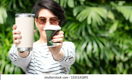 A stylish beautiful woman holding takeaway coffee cup in both hands, one is a squeezed single use paper cup with plastic lid the other one is a reusable stainless tumbler. No straw, Say no to plastic.
