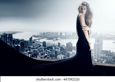 Stylish beautiful woman posing in black elegant dress. Skyline on background.