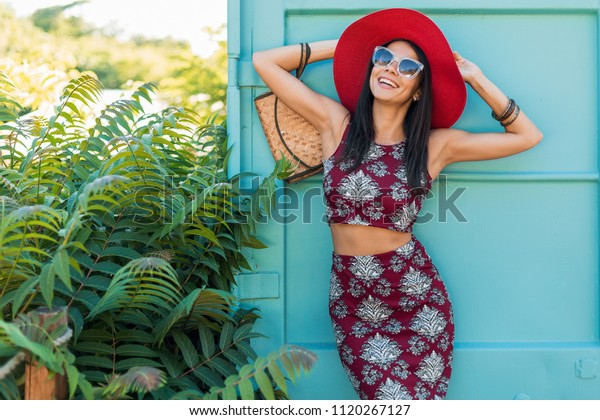 stylish beautiful woman in red hat posing on blue background, printed outfit, summer style, fashion trend, top, skirt, skinny, straw handbag, sunglasses, accessories, smiling, happy, tropical vacation