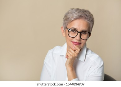 stylish beautiful woman with a short haircut, in a white shirt on a beige background