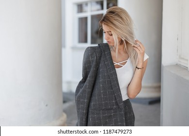 Stylish beautiful young blond model woman in a white t-shirt with a gray vintage jacket and pants in a city on the street
