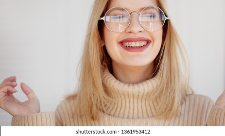 Stylish and beautiful young blonde with glasses and beige oversize sweater. Young woman wearing braces and smiling