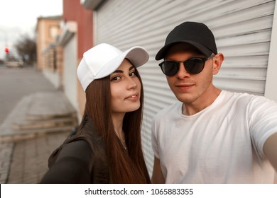 Stylish beautiful young couple in fashionable clothes with sunglasses and a cap travel and make a photo of a selfie.  Pretty model woman with handsome man