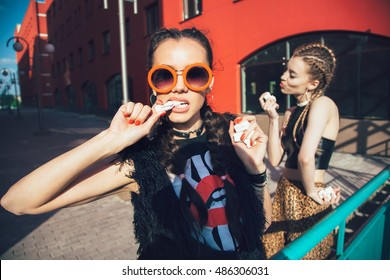 Stylish beautiful young female models in vintage cloth eating sweats, marshmallows. Outdoors lifestyle toned portrait