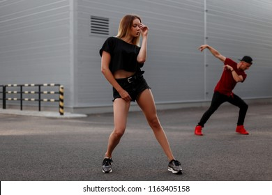 Stylish beautiful young hip-hop woman dancer with black fashion clothes dancing outside. Dancer man on the background