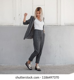 stylish beautiful young woman in a gray jacket with a white T-shirt and gray fashionable pants with shoes posing on the street. Fashion business style clothes