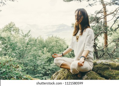 Stylish beautiful young woman practicing yoga in pose of lotus on cliff in summer forest outdoor.