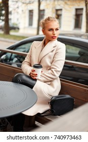 Stylish beautiful young woman in trendy coat with coffee sitting on the terrace