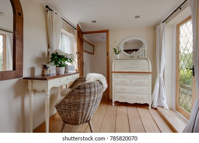 Stylish beautifully decorated entrance lobby withing a traditional cottage with writing Bureau, wicker chair, side table, mirror, timber floor and glazed entrance door