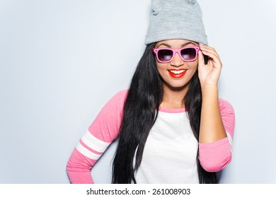 Stylish beauty. Happy young African woman in funky clothes adjusting her sunglasses and smiling while standing against grey background