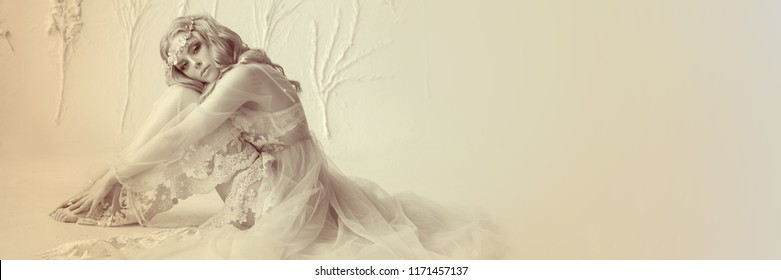 Stylish beauty portrait of a young girl model, warm toning. The image of the bride, a light lace dress, a beautiful hairstyle and a natural make-up. Light photo studio, natural light from the window.