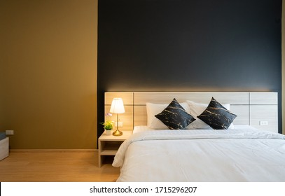 Stylish Bedroom corner with wooden headboard and bed with soft pillows setting with navy blue and yellow painted wall on the background / cozy interior design / modern interior