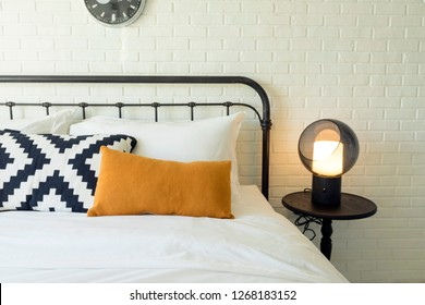 Stylish bedroom decorated with orange  pillows and clock on wall. Interior concept