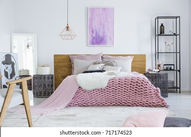 Stylish bedroom designed for a model with fashion poster and comfortable pink bed with wooden bedhead