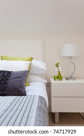 Stylish bedroom detail with intricate fabrics, cushions, pillows, duvet and side table including lamp