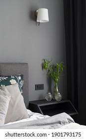 Stylish bedroom with gray wall, black window curtains and comfortable bed and with simple, black bedside table with glass decorations and plants