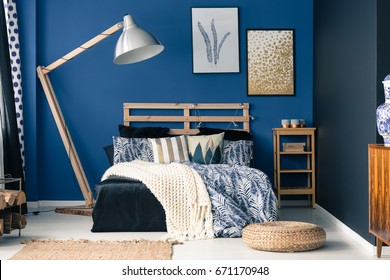 Stylish bedroom interior with dark blue wall