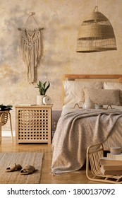 Stylish bedroom interior with design coffee table, furniture, plant, carpet, rattan decoration and elegant personal accessories. Beautiful beige bed sheets, blanket and pillows. Template.