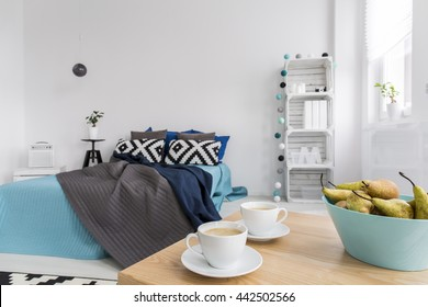 Stylish bedroom with large bed, two coffees standing on wood table