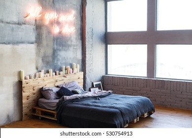 Stylish bedroom in loft style with grey colors and many candles. Bed with dark grey blanket