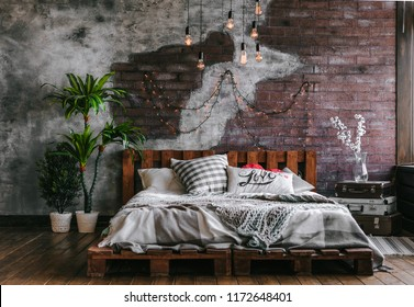 Stylish bedroom in loft style with lots of pillows and lots of light bulbs. Bed on brick wall background. Modern loft bedroom design.
