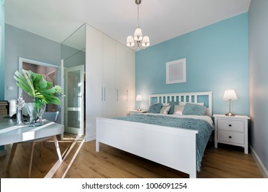 Stylish bedroom with mirror wall in pastel colors