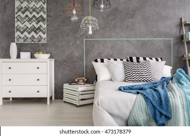Stylish bedroom with white furniture and decorative wall plaster