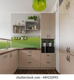 Stylish beige furniture in kitchen with green elements