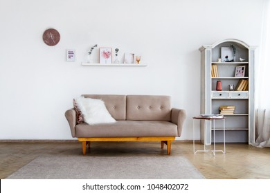 A stylish beige sofa with a white fluffy pillow in a spacious bright living room with a buffet
