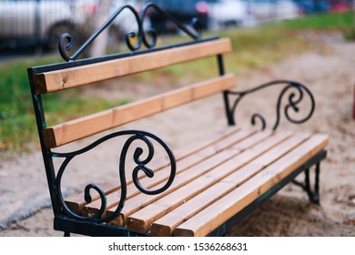 Stylish bench in the summer park. Metal and wood bench outdoors. Lonely benches in the park on late summer afternoon.