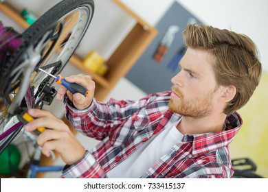 stylish bicycle mechanic doing his professional work in workshop