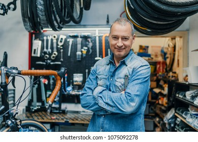 Stylish bicycle mechanic standing in his workshop. The best bicycle repair man in town. Bicycle Mechanic. A man working in a bicycle repair shop