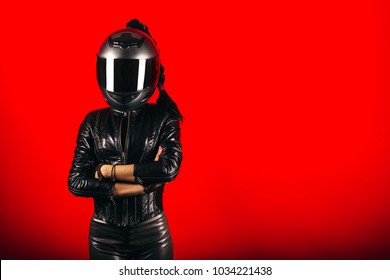 Stylish biker girl in helmet posing in studio on a red background
