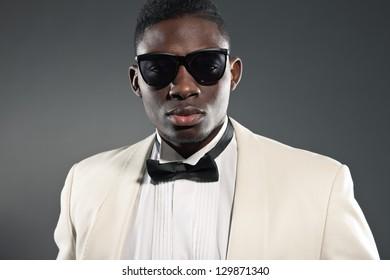 Stylish black american man in suit with sunglasses. Fashion studio shot.