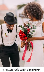 Stylish black groom in hat and his charming bride happily laughing on their wedding ceremony