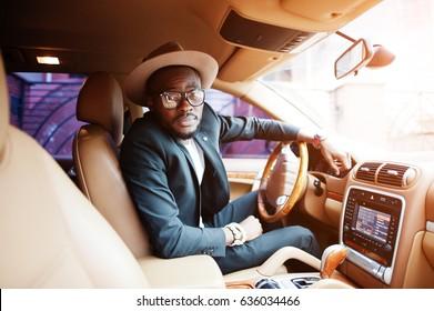 Stylish black man sitting behind the wheel of luxury car. Rich african american businessman.