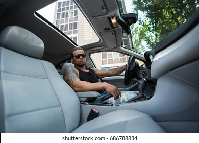 Stylish black man sitting behind the wheel of luxury car.