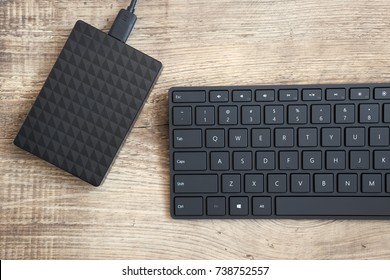 stylish black wireless keyboard and external hard disc drive on a wooden surface.  Top view.