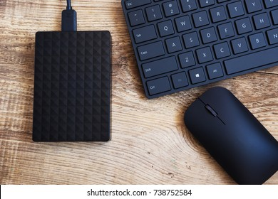 stylish black wireless keyboard, mouse  and external hard disc drive on a wooden surface