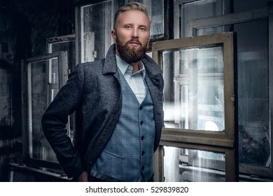 Stylish blond, bearded male dressed in an elegant, classic jacket posing on old, vintage windows background.