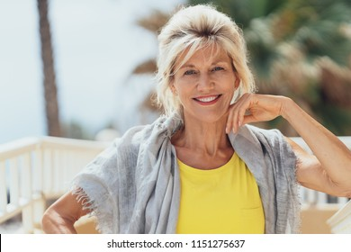 Stylish blond woman sitting on a balcony with a shawl over her shoulders in the sunshine smiling at the camera