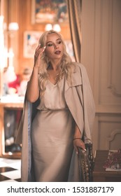 Stylish blonde with curly hair woman 20-24 year old wearing beige dress and jacket posing in cafe. Fashionable lady. 20s.